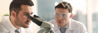 Two technicians working in a laboratory and carrying out microscope analyses